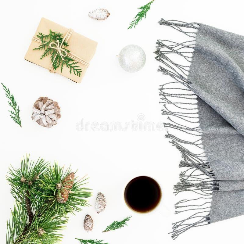 Украшения рождества, шарф, ветвь сосны, кофейная чашка и подарок на белой предпосылке Плоское положение, взгляд сверху Рождество, стоковое фото