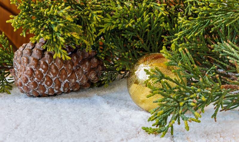 Украшения рождества, конусы сосны и ветвь рождественской елки в t стоковые фото
