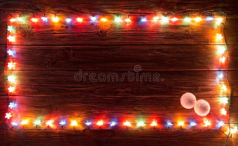 Украшения света рождества на деревянной текстуре стоковые фото