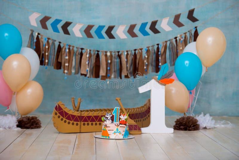 Украшенная зона фото для вождя апаша индейца 1 года с каноэ для партии детей Первый торт дня рождения и огромного успеха стоковые изображения