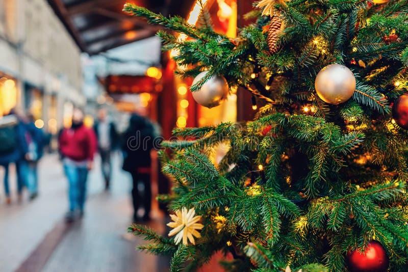 Украшенная рождественская елка на рынке traditonal в вечере стоковое фото