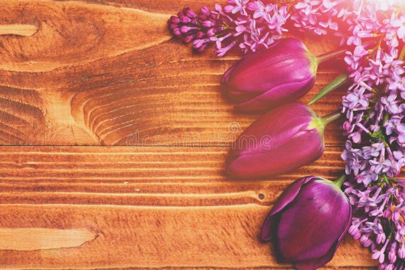 Украшенная теплая коричневая деревянная поверхность с фиолетовыми тюльпаном и сиренью стоковая фотография