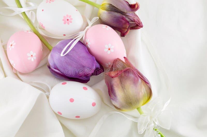 Украшенные пасхальные яйца и фиолетовые тюльпаны стоковое изображение