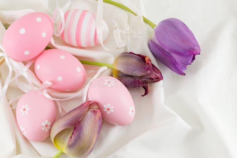 Украшенные пасхальные яйца и фиолетовые тюльпаны стоковые фотографии rf