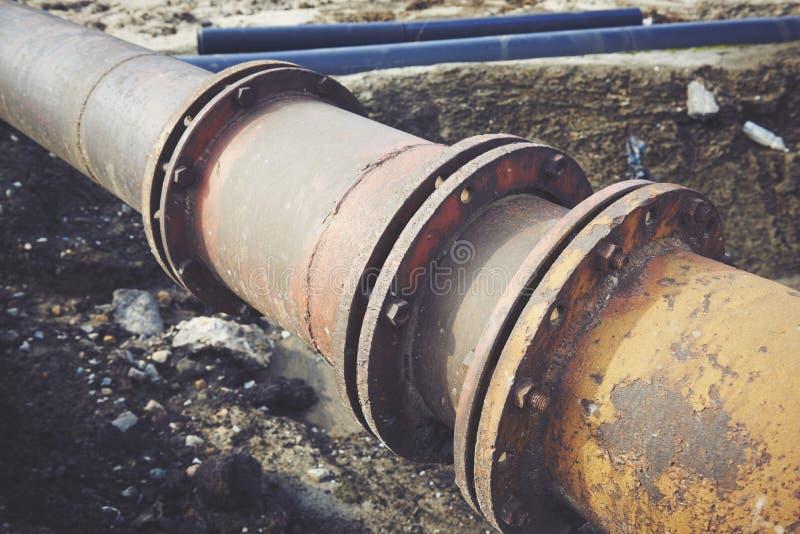 Украдите большой трубопровод на земле Старое соединение труб стоковые изображения