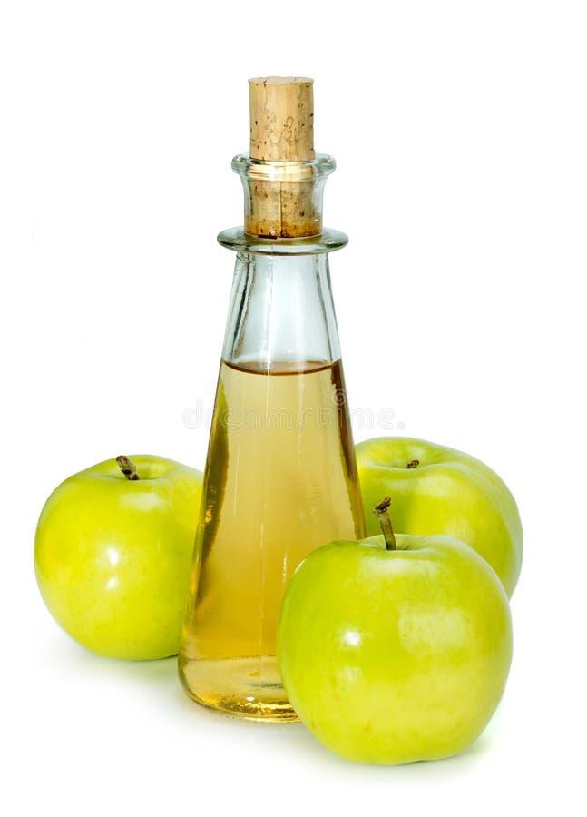 Уксус яблочного сидра в стеклянном сосуде и зеленых яблоках стоковое изображение