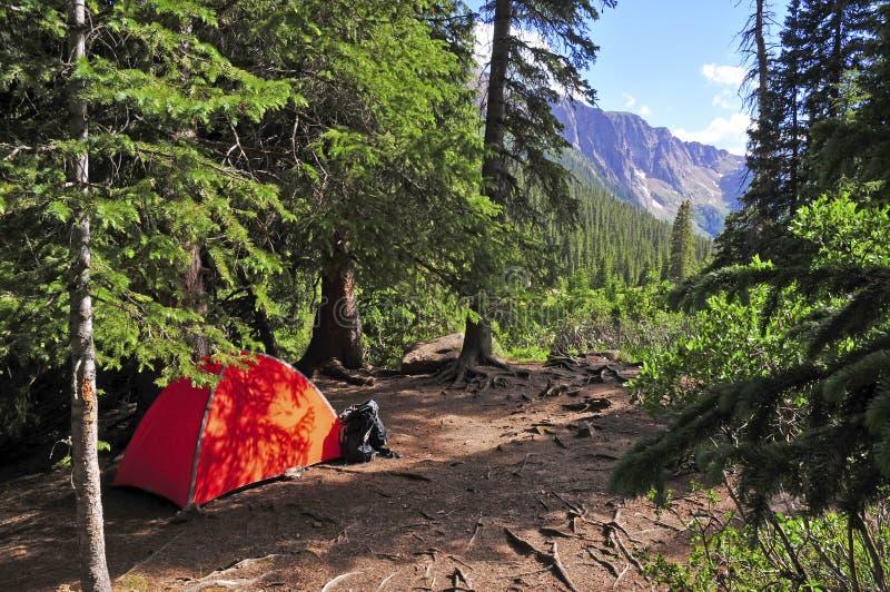Укладывать рюкзак: Располагаться лагерем с шатром в горах стоковые изображения