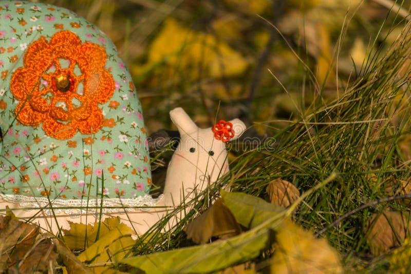 Улитка игрушки ткани вползая на желтых листве и траве : o стоковое изображение rf