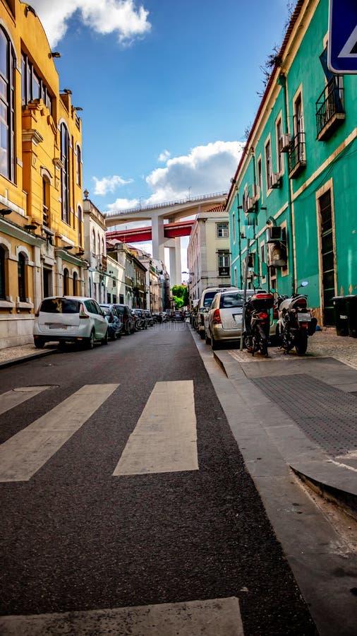 улица в Лиссабоне Португалии с мостом 25 de abril на заднем плане и красивыми домами и припаркованными автомобилями дата 2-ое июл стоковые фотографии rf