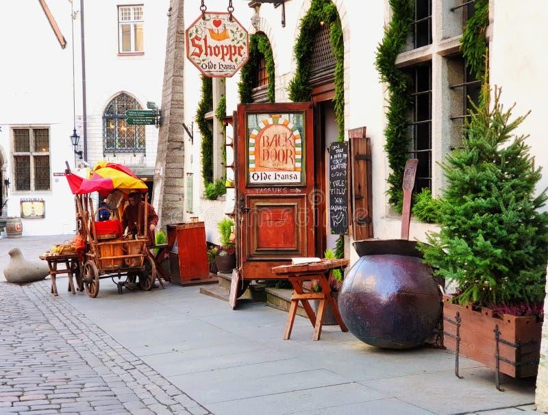 Улица в старом Таллинне, Эстонии рождественская елка и старая торговая тележка с красной палаткой находится рядом со средневеково стоковое изображение rf