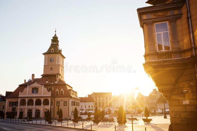 Улица города центральная с взглядом восхода солнца утра башни залы городского совета, положением Brasov, Трансильванией, Румынией стоковое фото