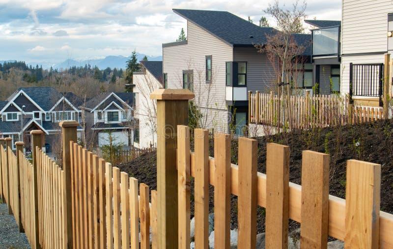 Улица домов семьи в пригородном районе с конкретными бортовой прогулкой и дорогой асфальта во фронте Жилые дома стоковое фото rf