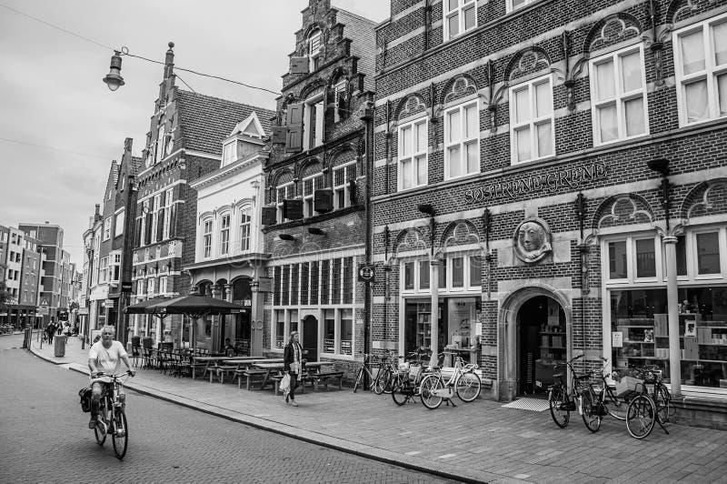 Улица при рестораны, магазины, велосипедист и люди гуляя в s-Hertogenbosch к центру города стоковое фото