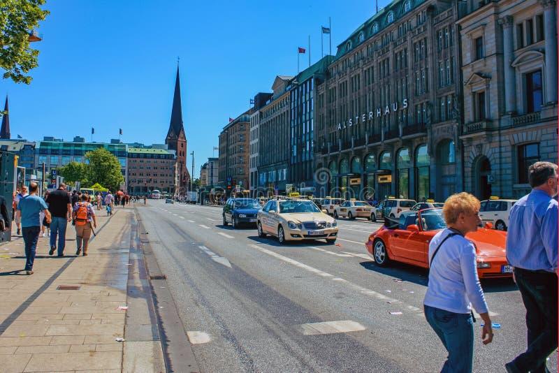 Улица с людьми и автомобилями около станции метро Alsterhaus и озера Alster Binnenalster Гамбурга, Германии стоковое изображение