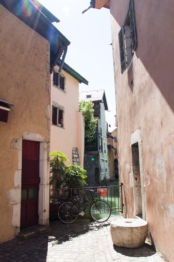 Улицы Анси со старинными зданиями, велосипедом и каналом на солнечный день стоковые фото
