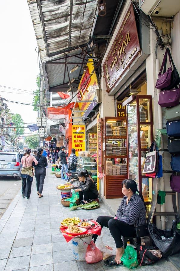 Уличные торговцы продавая различные типы плодоовощей и закусок около улицы в квартале Ханоя старом стоковые фото