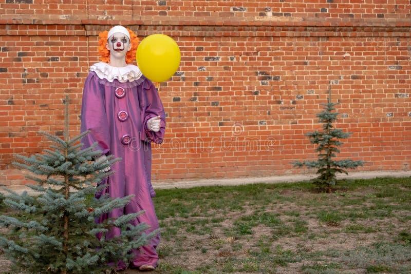 Уличный артист в костюме злого страшного клоуна, похожего на Пенниуол, рядом с деревом, сажающим деревья Парень, похожий на ИТ стоковые изображения rf