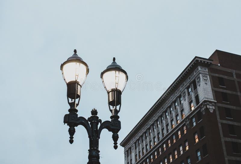 Уличный свет на ноче с зданием позади стоковое фото