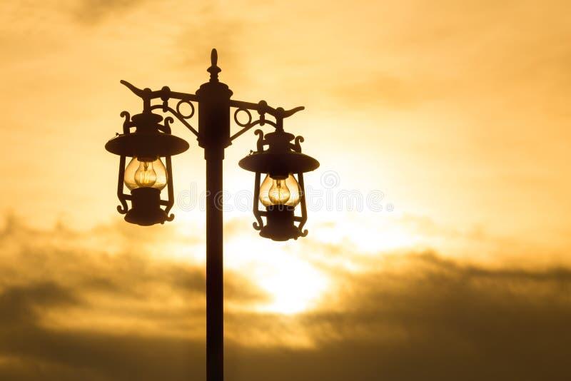 Уличный фонарь силуэта чугунный на заходе солнца стоковое фото