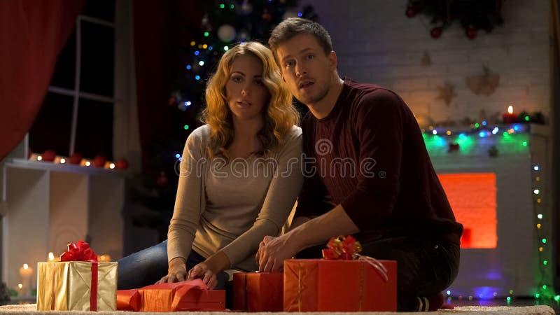 Уловленные родители пока пакующ X-mas настоящие моменты под рождественской елкой, разочарование стоковые изображения rf
