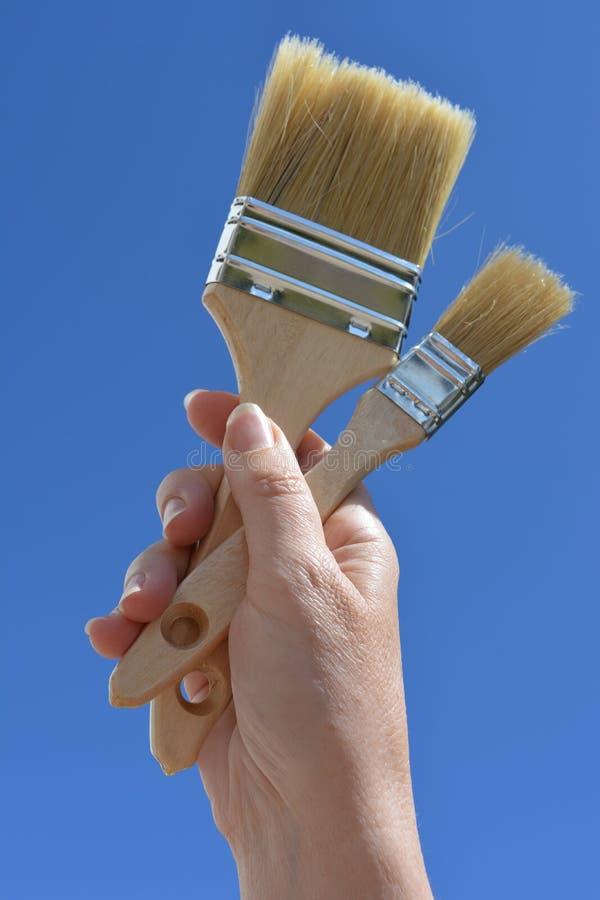 Улучшения дома и DIY, рука держа кисти стоковые фото