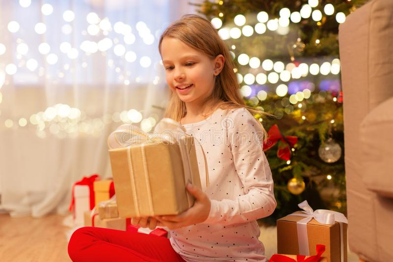 Улыбающаяся девушка с подарком на Рождество дома стоковые фото