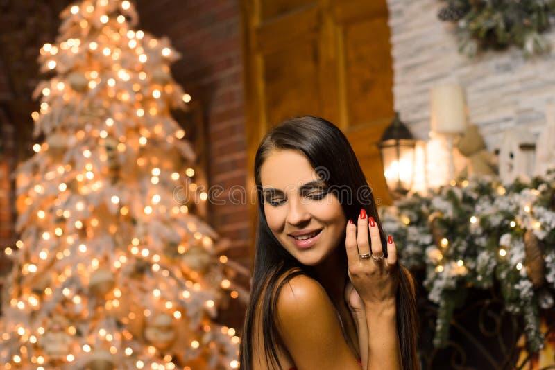 улыбающаяся женщина на заднем плане новогоднего дерева и огни из гарландов, бокех стоковое изображение