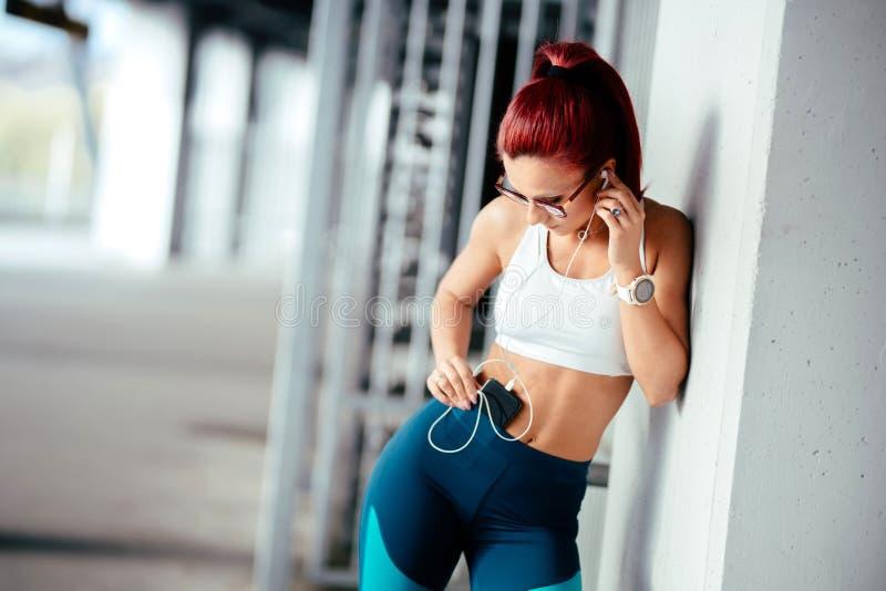 улыбающаяся женщина, слушающая музыку и обучающаяся Современная фитнес-концепция с технологическими гаджами стоковая фотография
