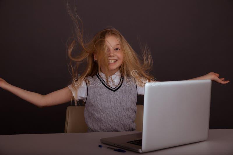 Улыбающаяся счастливая девушка сидит рядом с ноутбуком и весело провоРстоковая фотография