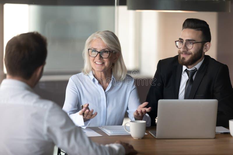 Улыбающиеся менеджеры проводят интервью с кандидатом на хорошую работ стоковое фото rf