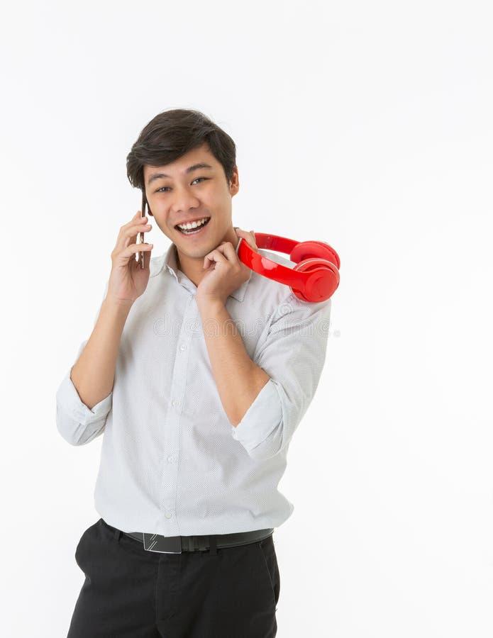 Улыбающийся азиатский мужчина говорит на смартфоне и держит красный нРстоковое изображение