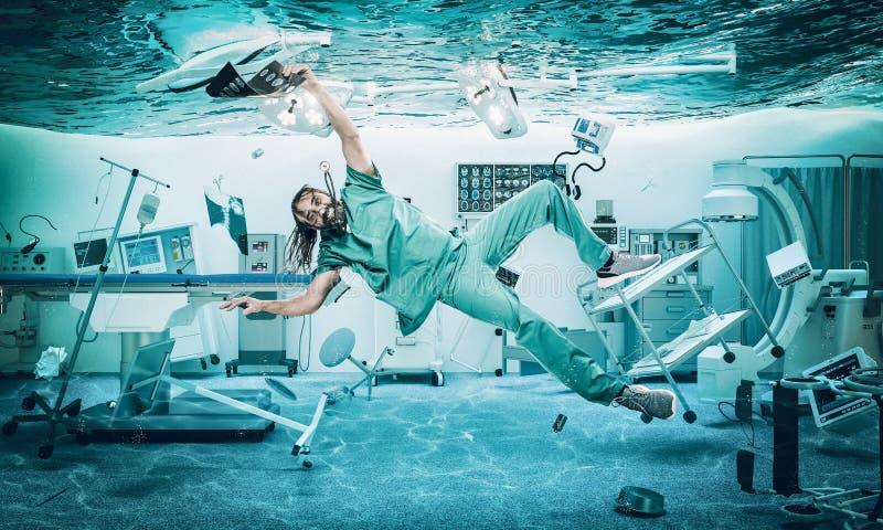 Улыбающийся врач плывет под водой в затопленной операционной стоковое фото rf