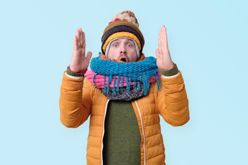Улыбающийся тысячелетний кавказец в зимней шляпе и шарфе показывает большой размер обеими руками стоковая фотография rf