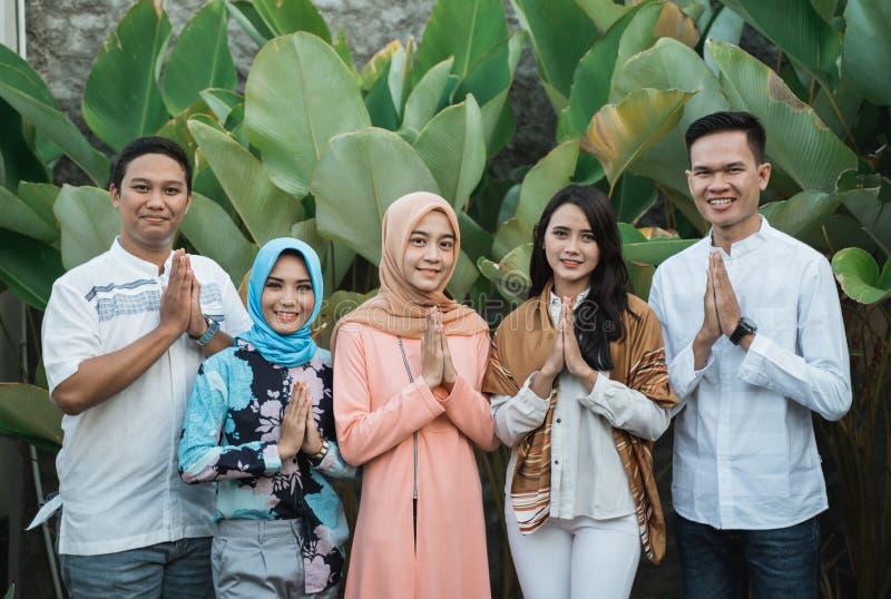 Улыбка группы друзей жестом извиняется когда Eid стоковое изображение rf