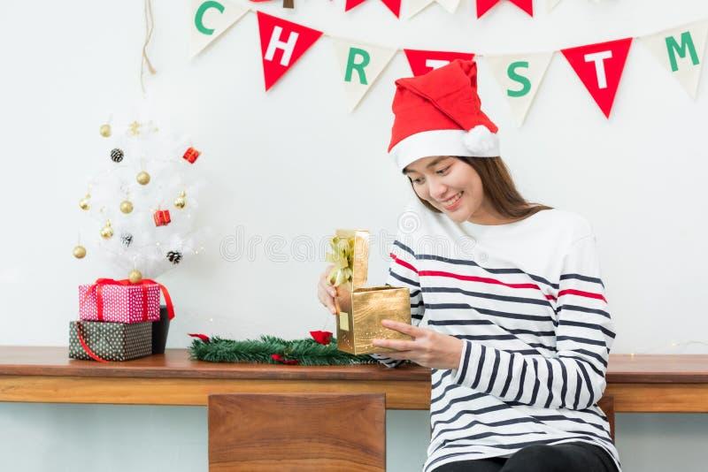 Улыбка женщины Азии когда открытая подарочная коробка xmas золота на партии праздника w стоковое изображение rf
