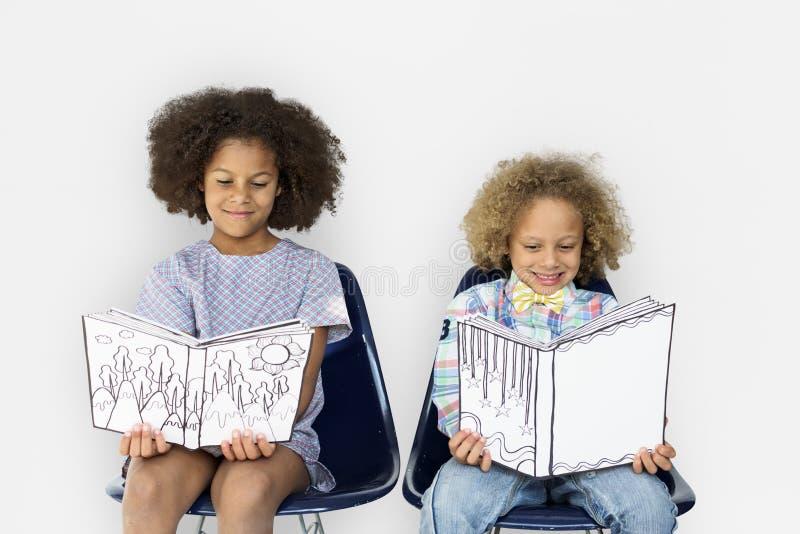 Улыбка книги чтения маленьких детей стоковое изображение rf