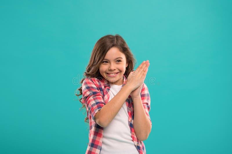 Улыбка маленького ребенка возбужденная с новой стойкой идеи над голубой предпосылкой Это пункт Решение идеи милая девушка стоковое фото rf