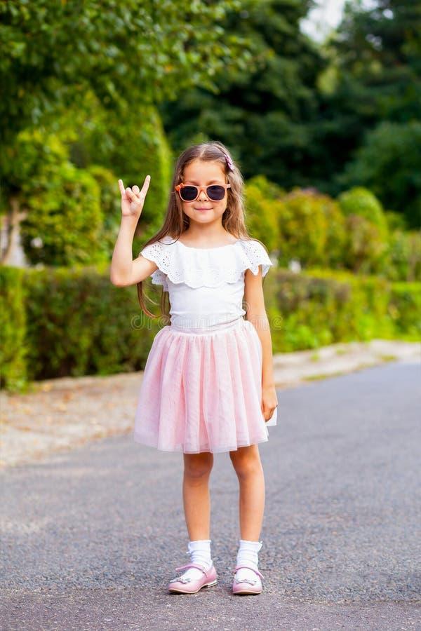 Улыбка маленькой девочки в солнечных очках на улице Вертикальное фото стоковое изображение rf