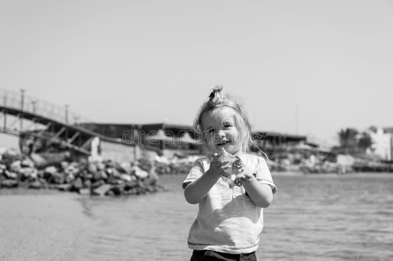 Улыбка мальчика с раковиной на пляже моря Детская игра с seashell на солнечном seascape Свобода, открытие и приключение стоковые фотографии rf