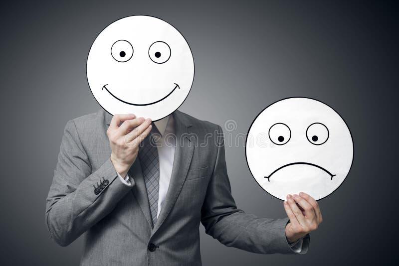 Улыбка удерживания бизнесмена и унылая маска Схематическое изображение человека изменяя его настроение от плохого к хорош стоковое фото