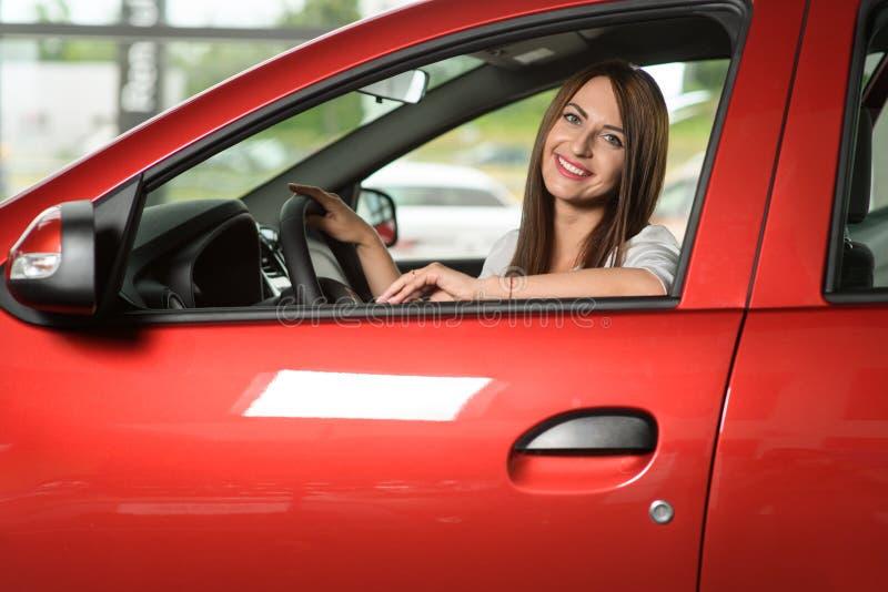 Улыбки девушки в новом автомобиле стоковые фото