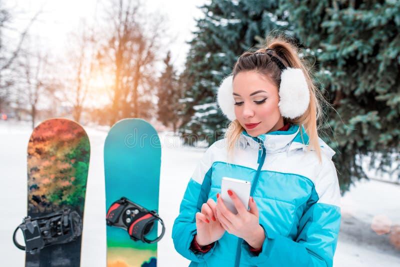 Улыбки женщины в зиме на курорте на предпосылке снега и елей Сноуборды, мобильный телефон, болтовня онлайн стоковые фото