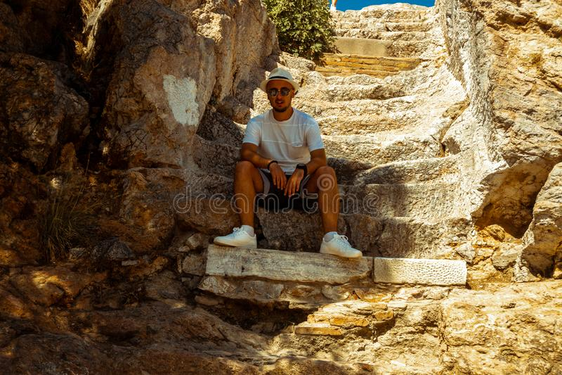 Улыбки человека на камере сидят на лестницах древнегреческого стоковое фото rf
