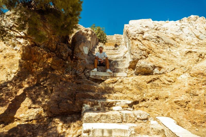 Улыбки человека на камере сидят на лестницах древнегреческого стоковые фотографии rf