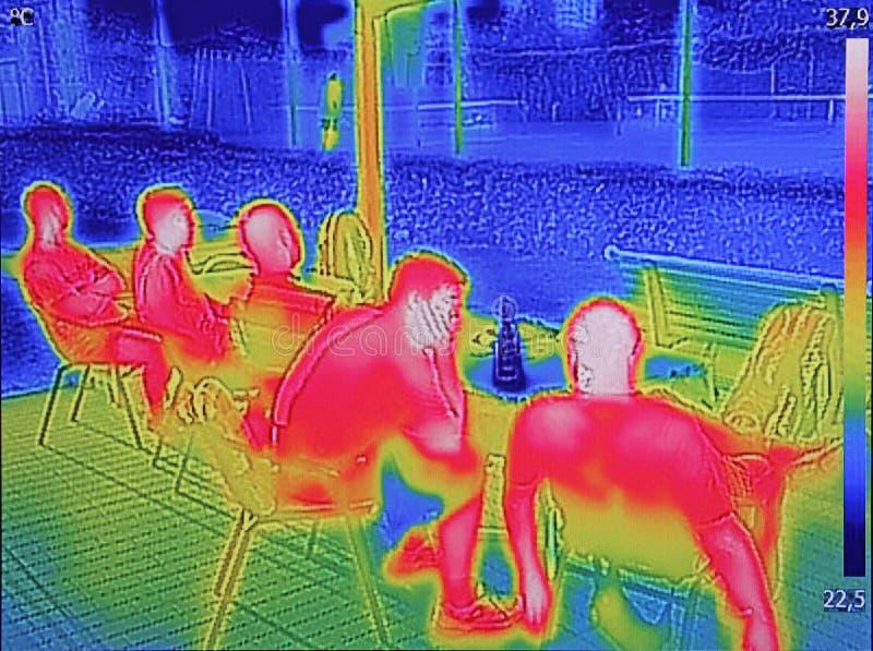 Ультракрасный показ изображения thermovision когда люди сидят на таблице стоковая фотография rf