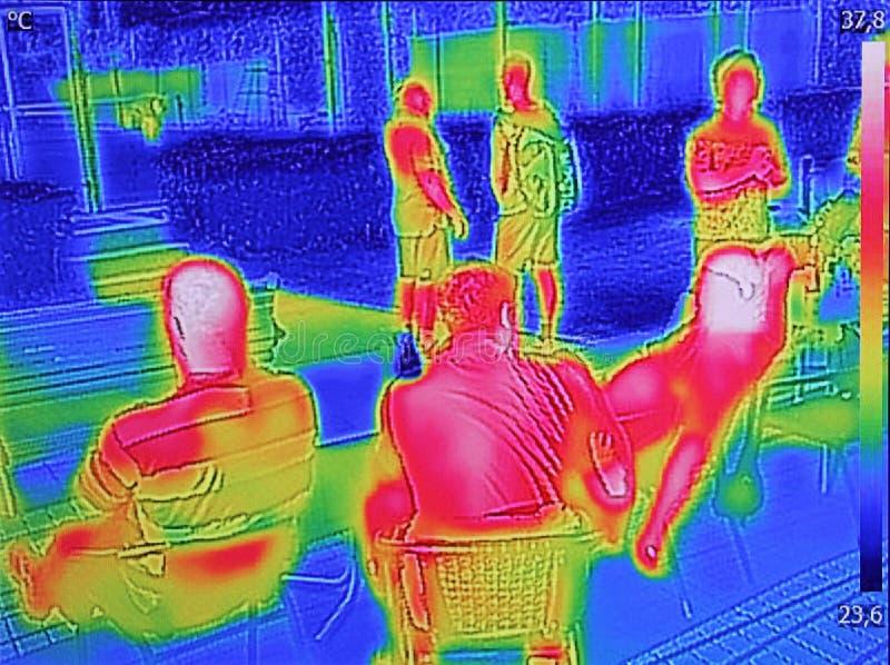 Ультракрасный показ изображения thermovision когда люди сидят на таблице стоковая фотография