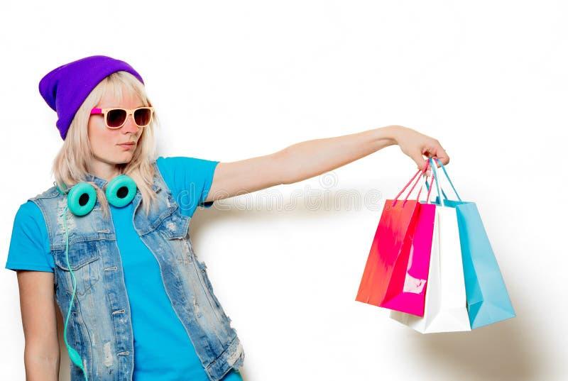 Ультрамодная девушка в шляпе с хозяйственными сумками стоковое изображение