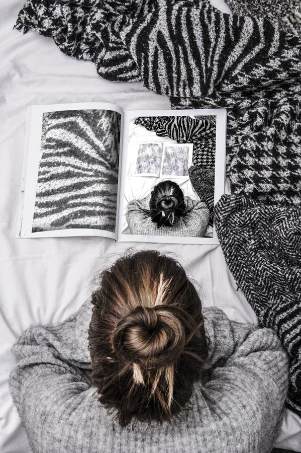Ультрамодная женщина битника лежа в ее кровати и читая журнал о моде на уютном воскресенье стоковое фото rf