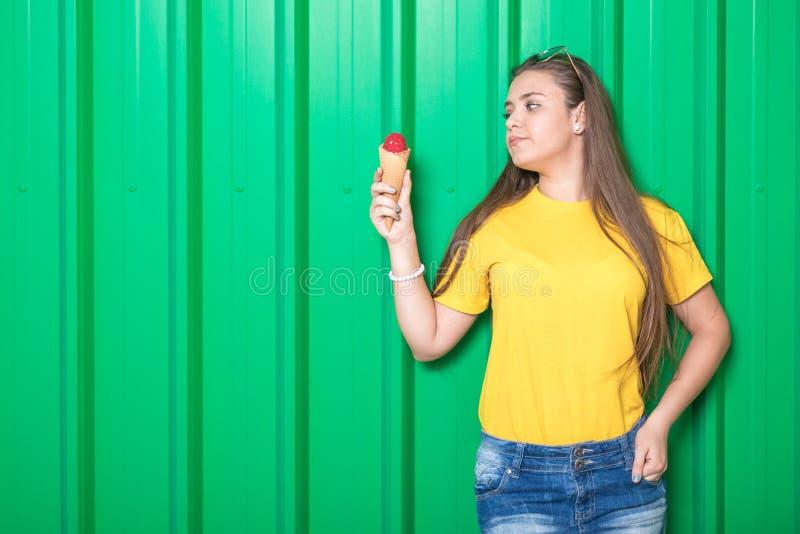 Ультрамодное предназначенное для подростков с мороженым на зеленой предпосылке стены стоковые фотографии rf