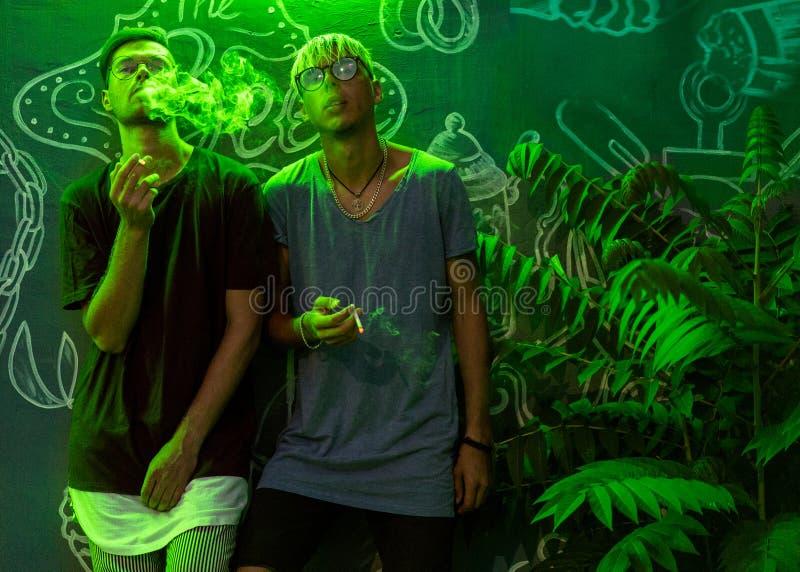 Ультрамодные парни моды куря в неоновом зеленом свете стоковое фото rf